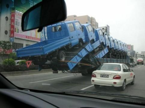 Zehn LKWs werden auf einem anderen LKW transportiert.