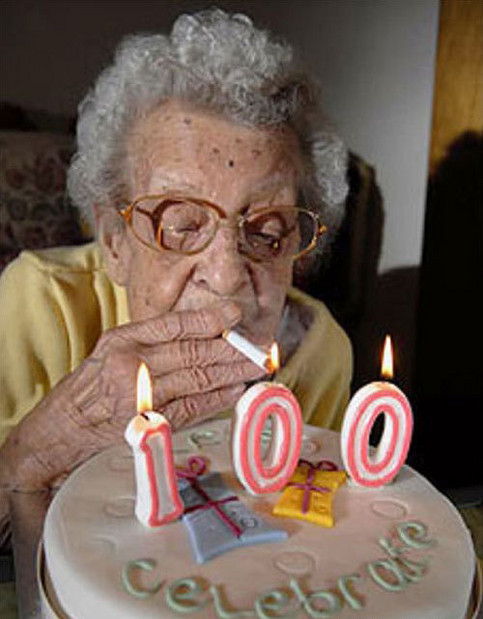 Eine Oma zündet sich an den Kerzen auf einer Torte zum 100. Geburtstag eine Zigarette an.