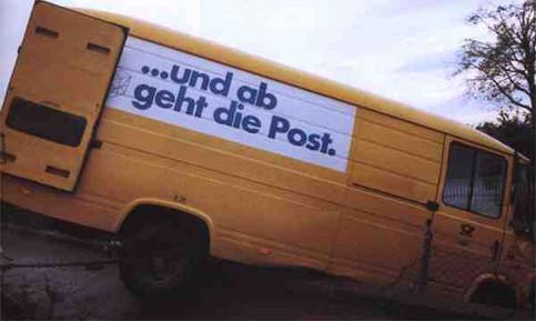 """Ein Post-Transporter mit der Aufschrift """"...und ab geht die Post"""" ist durch einen Zaun einen Abhang hinunter gefahren."""