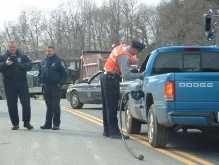Ein Auto wird von der Polizei mit einem abgerissen Tankrüssel im Tank angehalten.