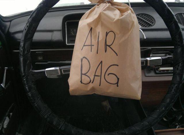 """An einem alten Lenkrad eines PKWs wurde eine Papiertüte mit der Aufschrift """"Air Bag"""" befestigt."""