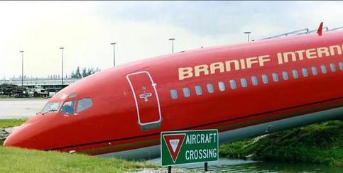 """Ein Flugzeug neben einem Schild """"Aircraft crossing""""."""