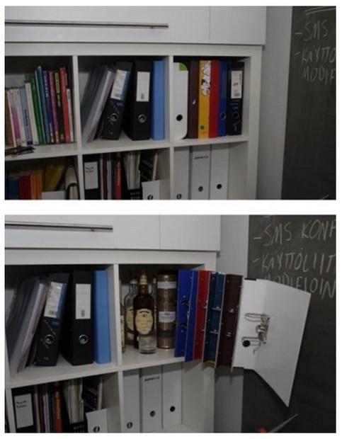 Hinter einer Fassade aus Aktenordnern ist in einem Büroschrank eine Sammlung von Flaschen mit Alkohol versteckt.