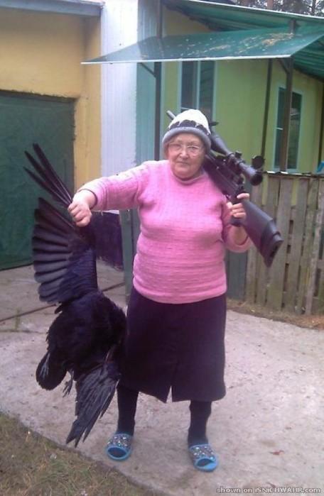 Eine alte Frau mit Wollpullover und Mütze hat ein Gewehr auf der Schulter. In der anderen Hand hält sie einen großen Vogel.