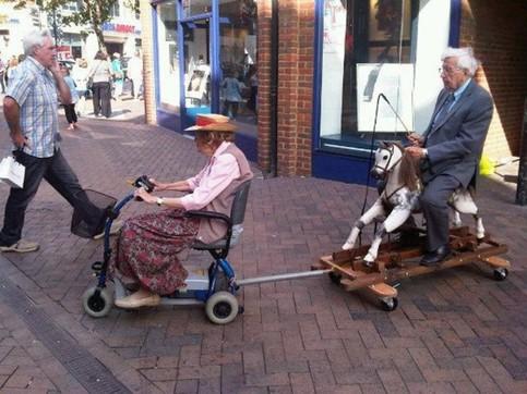 Eine alte Frau in einem elektrischen Rollstuhl zieht einen alten Mann auf einem Holzpferd hinter sich her. Der Mann hat eine Peitsche in der Hand.