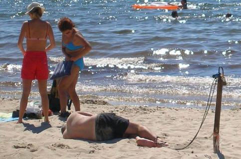 Ein Mann ist an einem Strand an einer Kette angebunden und schläft.