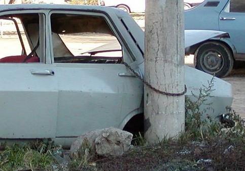 Ein Auto ist mit einer Kette an einen Baum gekettet.
