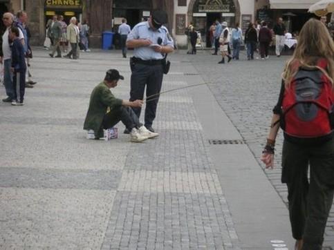 Ein Mann angelt durch einen Gully-Deckel und bekommt dafür einen Strafzettel von einem Polizisten.