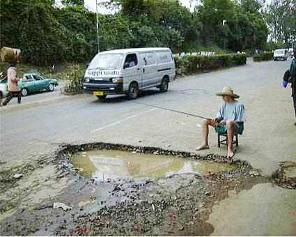 Ein Angler angelt in einem Schlagloch in einer Straße.