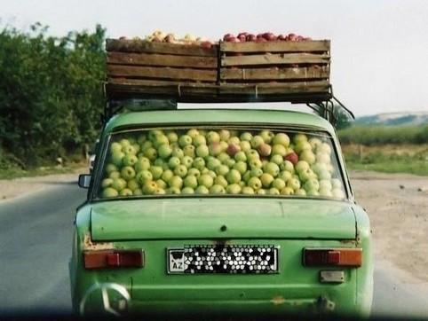 Ein Auto ist innen und auf dem Dach mit Äpfeln vollgestopft.