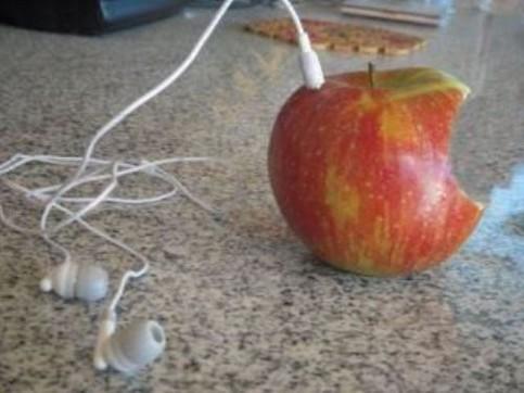 In einem angebissenen Apfel steckt ein Kopfhörer.