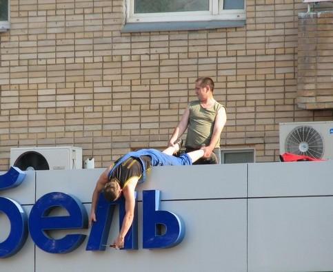 Ein Mann befestigt ein Schild, während er von einem anderen an den Beinen fest gehalten wird.