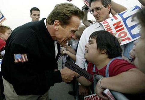 Arnold Schwarzenegger hält einem Kind eine Pistole vor die Brust.