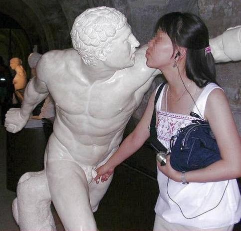 Eine Frau küsst eine Statue und greift an ihr Glied.
