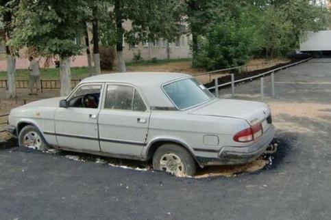 Ein Parklplatz wurde um ein Auto herum asphaltiert.