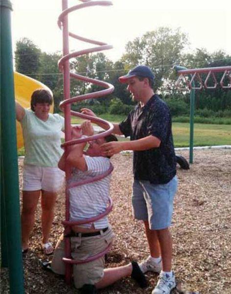 Ein dicklicher Junge ist auf einem Kinderspielplatz ist in einem Spielgerät stecken geblieben.