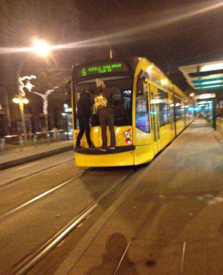 Zwei Männer halten sich aussen am einer Ende einer Straßenbahn fest und fahren schwarz. Eine gefährliche Aktion.