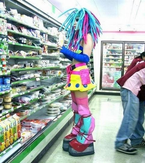 Eine Frau mit bunten Kleidern und blau-violetten Rastas steht in einem Supermarkt.