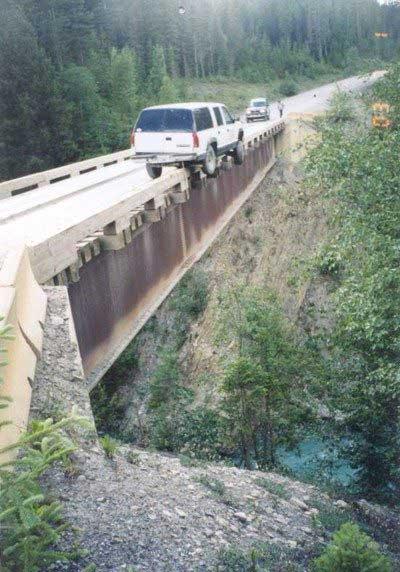 Ein Auto balanciert auf einem Brückengeländer über einem Abhang