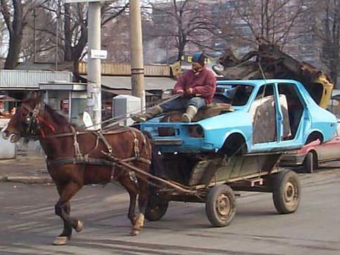 Ein Auto wird auf einem Karren von einem Pferd gezogen.