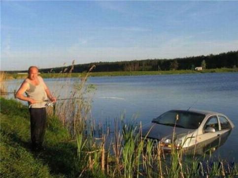 Ein Auto ist halb in einem See versunken. Ein Mann steht mit einer Angel daneben und tut so, als würde er das Auto an Land ziehen.