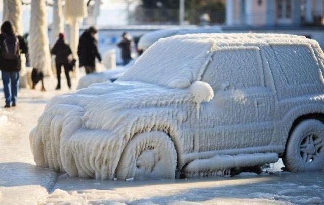 Ein Auto ist komplett und zentimeterdick mit Eis überzogen.