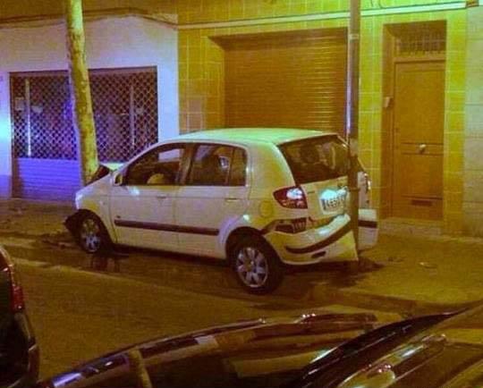 Ein Auto ist zwischen einem Baum und einem Laternenpfahl eingeklemmt.