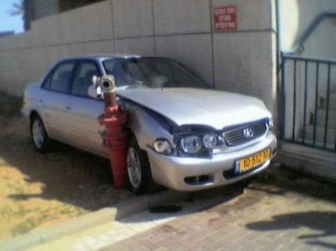 Ein Auto ist zwischen einer Wand und einem Hydranten eingequetscht.