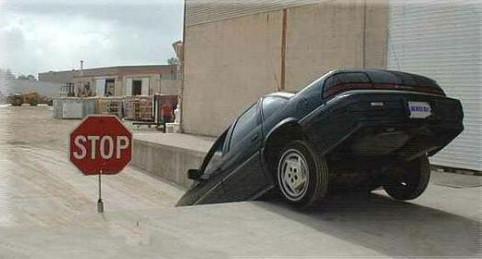 Ein Auto ist an einem STOP-Schild vorbei in ein Loch gefallen.