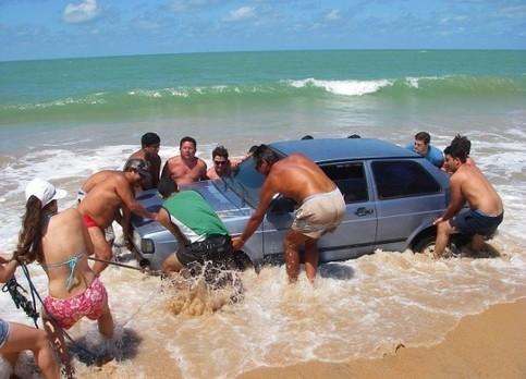 Menschen versuchen, ein Auto am Strand vor der Flut zuretten.