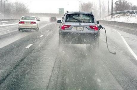 Ein Auto fährt auf einer Autobahn, im Tank hängt ein abgerissener Zapfhahn.