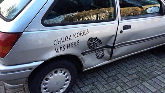 """Ein Auto hat eine Delle. Darüber wurde ein Aufkleber mit einem Schuhabdruck und der Spruch """"Chuck Norris was here"""" geklebt."""