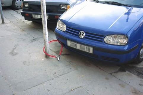 Ein Auto ist mit einem Fahrradschloss an einem Pfosten befestigt.
