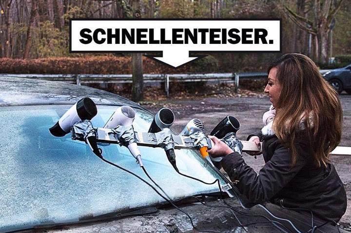 """Eine Frau enteist die Frontscheibe ihres Autos mit fünf Föns, die hintereinander an einer Stange befestigt wurden. Dabei steht """"Schnellenteiser""""."""
