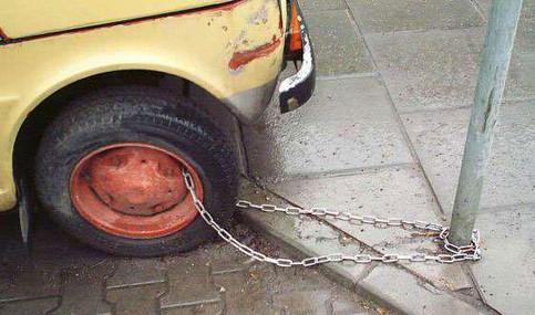 Ein Auto ist mit einer Kette an einem Pfosten befestigt.