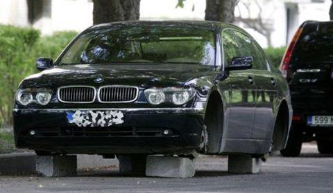 Ein BMW auf Ziegelsteinen mit gestohlenen Reifen.