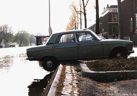 Ein Auto hängt mit den Hinterreifen über einem Fluss.