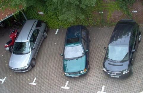 Ein Auto parkt quer auf einem Parkplatz.