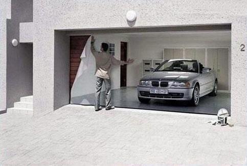 Eine Garage, die mit einem Plakat beklebt ist, so dass man glaubt, ein teures Auto stände in der Garage.