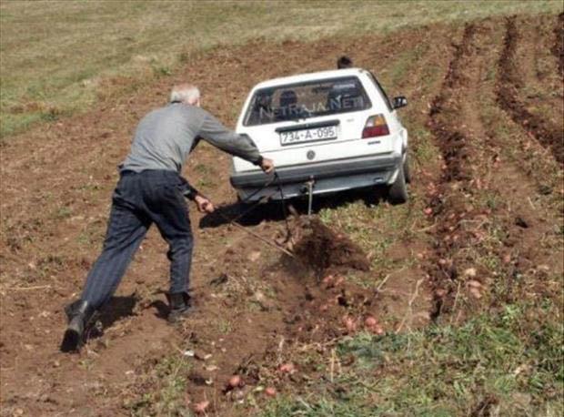 Ein Mann lässt einen Pflug von einem Auto ziehen und pflügt so sein Feld um.