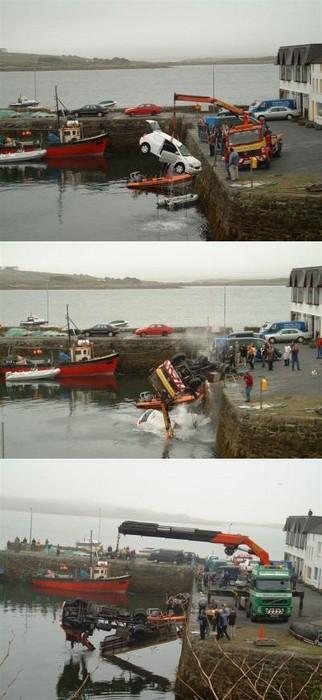 Ein Kran hebt ein Auto aus einem Hafenbecken, woraufhin der Kran selber ins Wasser fällt und er von einem größeren Kran geborgen wird.