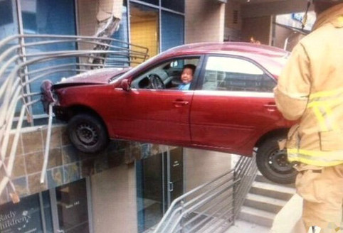 Ein Auto klemmt über einem Spalt fest. Ein Mann schaut aus dem Fenster heraus.