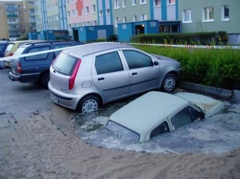 Ein Auto versinkt im Matsch einer Parklücke.