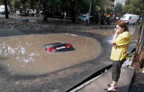 Ein Auto versinkt in einer Riesen-Pfütze.
