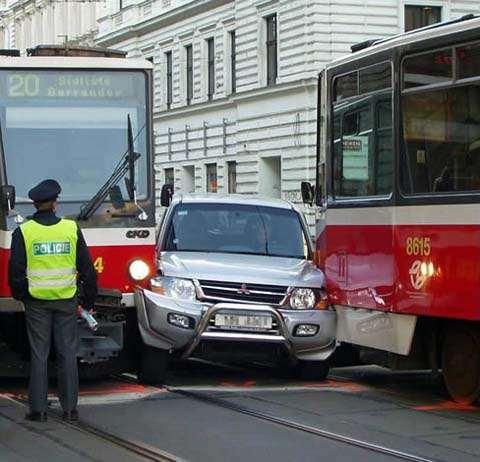 Ein Auto ist zwischen zwei Straßenbahnen eingeklemmt.