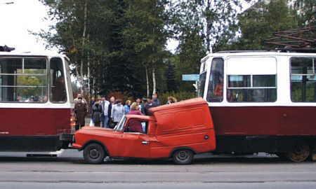 Ein Auto ist zwischen zwei Strassenbahnen eingeklemmt und zusammengequetscht.
