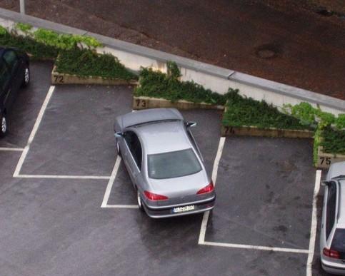 Ein Auto steht quer auf einem Parkplatz.
