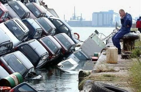 Eine Schiffsladung Autos ist am Sinken, ein Mann telefoniert daneben.