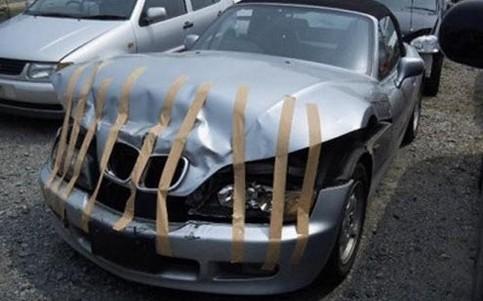 Ein BMW hatte einen Unfall. Die Motorhaube ist nur mit Klebeband zusammengeklebt.