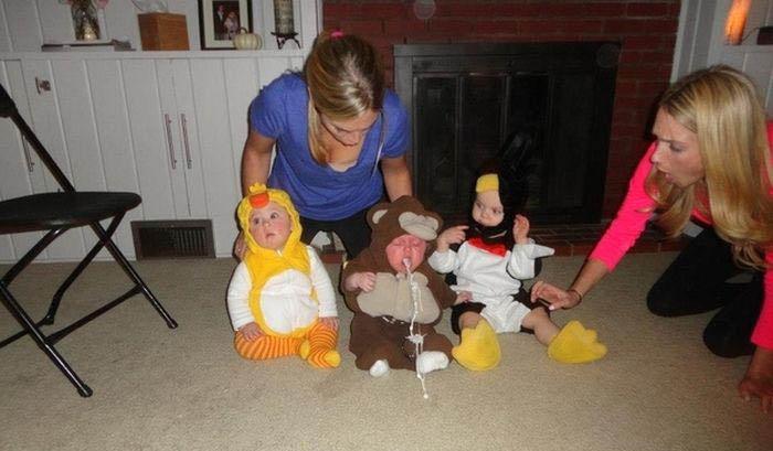 Drei verkleidete Babys sitzen auf dem Boden mit ihren Mamas. Eines der Babys bricht einen Strahl auf den Boden.